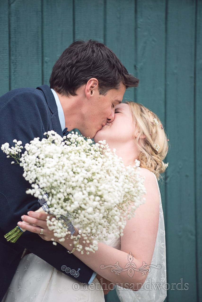 Bride and groom kiss infront of blue wooden slatted wall