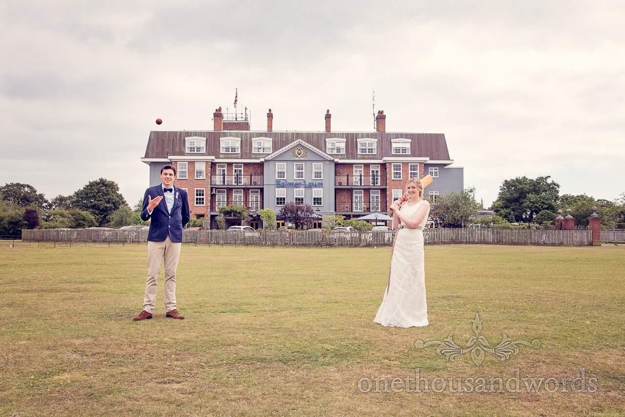 Bride and groom on cricket pitch outside Balmer Lawn Hotel Wedding venue