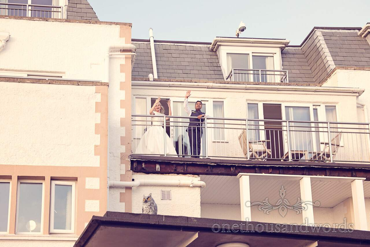 Bride and Groom wave from bridal suite balcony at Harbour Heights Hotel Wedding