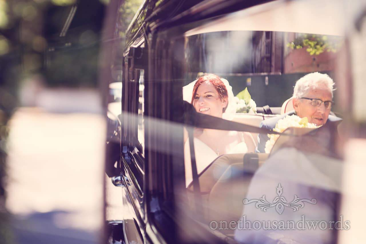 Bride and her father drive through Bournemouth in classic wedding car reflection