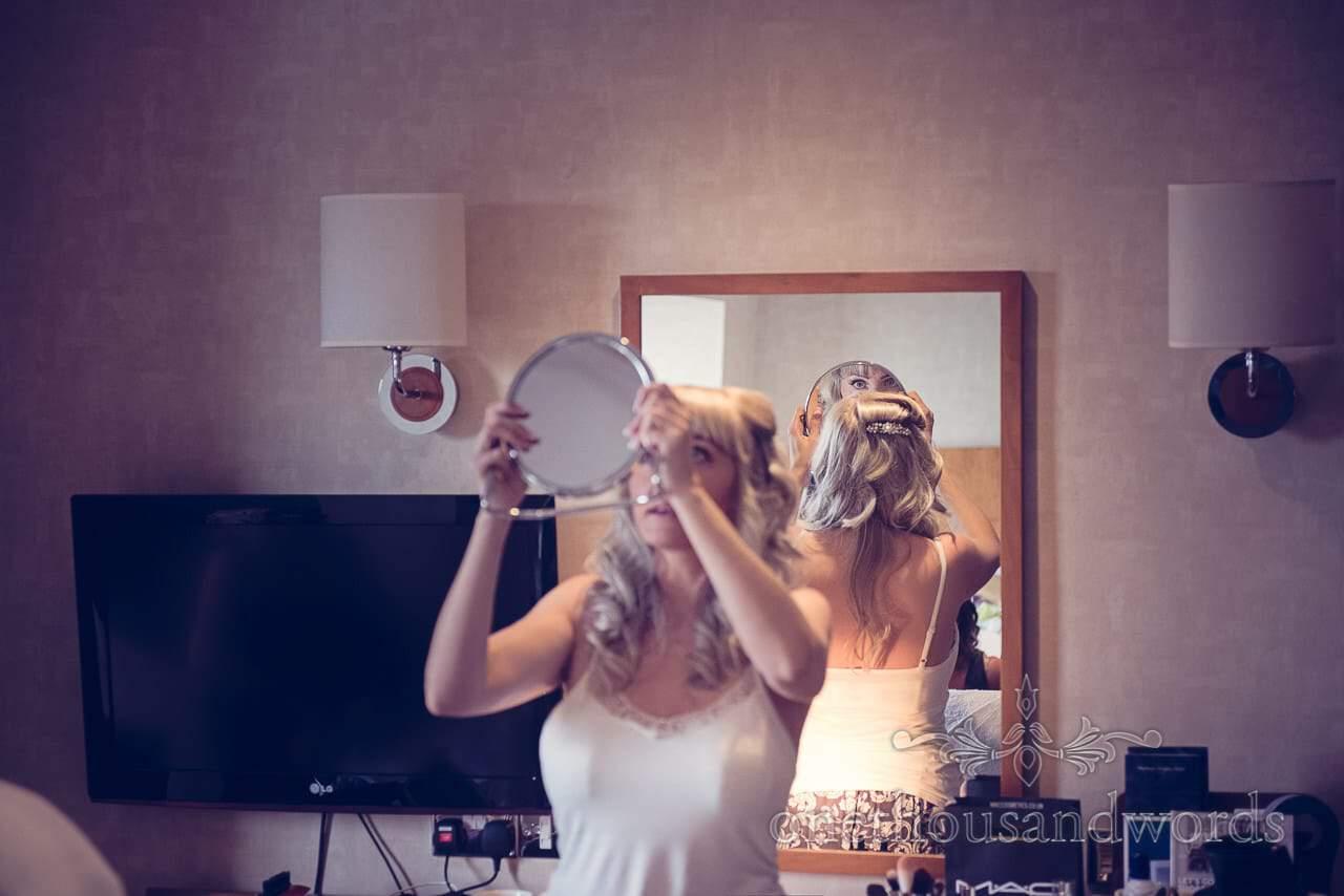 Bride checks her wedding hair style in mirror at Harbour Heights Hotel Wedding