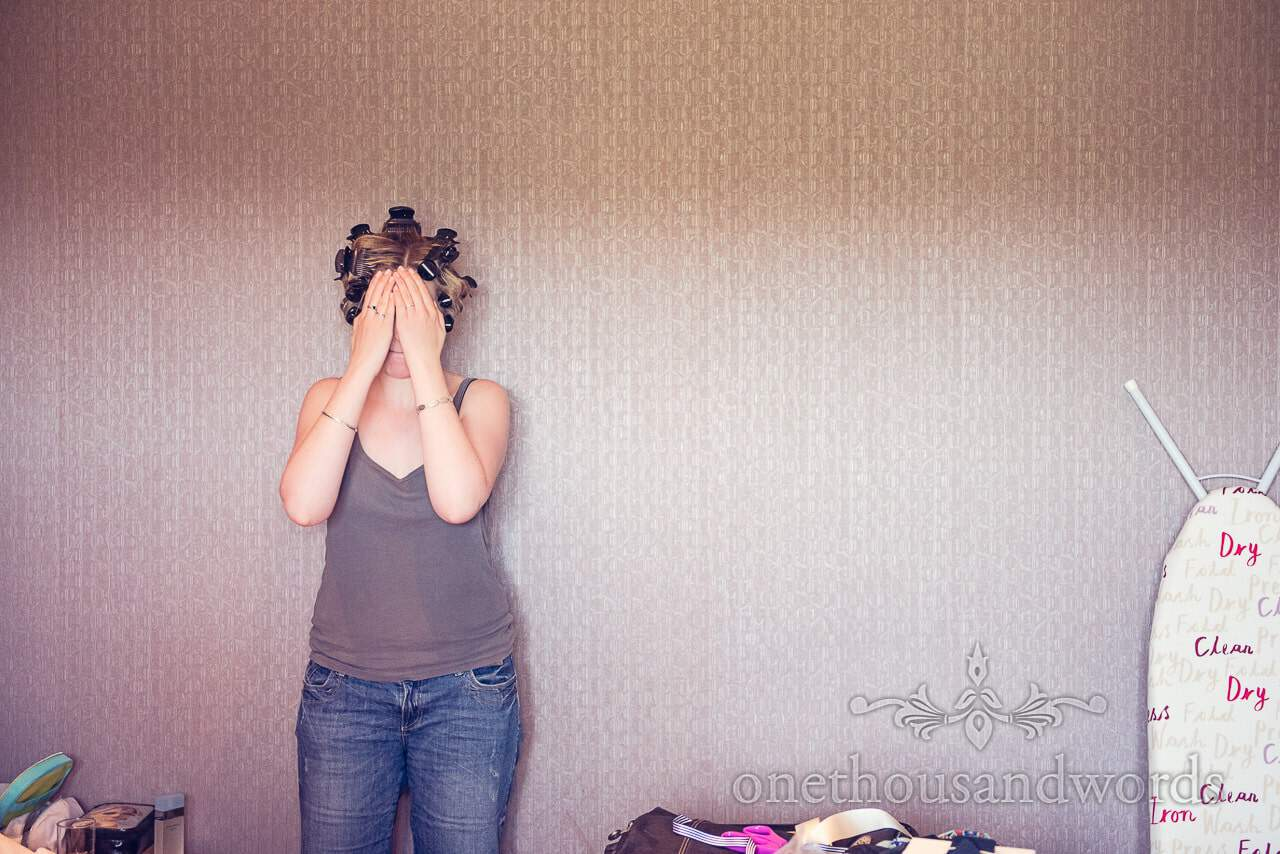 Bride covers her eyes in Balmer Lawn Hotel room during wedding preparations