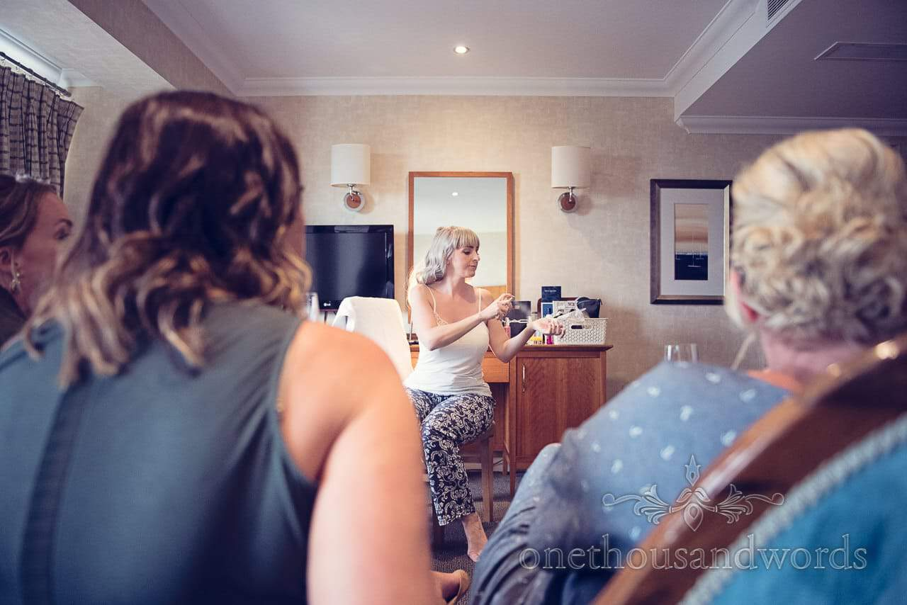 Bride sprays wedding perfume as she is watched by bridesmaids on wedding morning