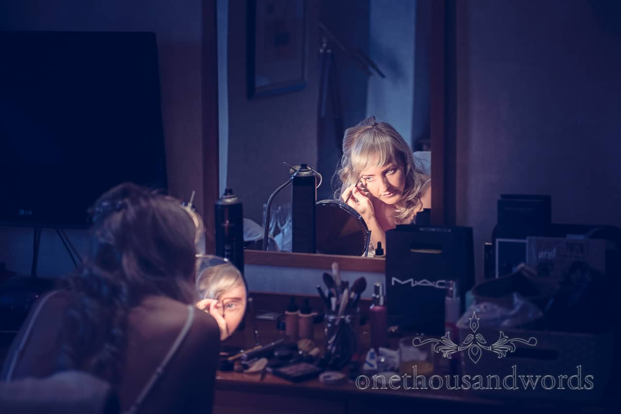 Bride stlyes her wedding makeup in mirrors at Harbour Heights Hotel Wedding
