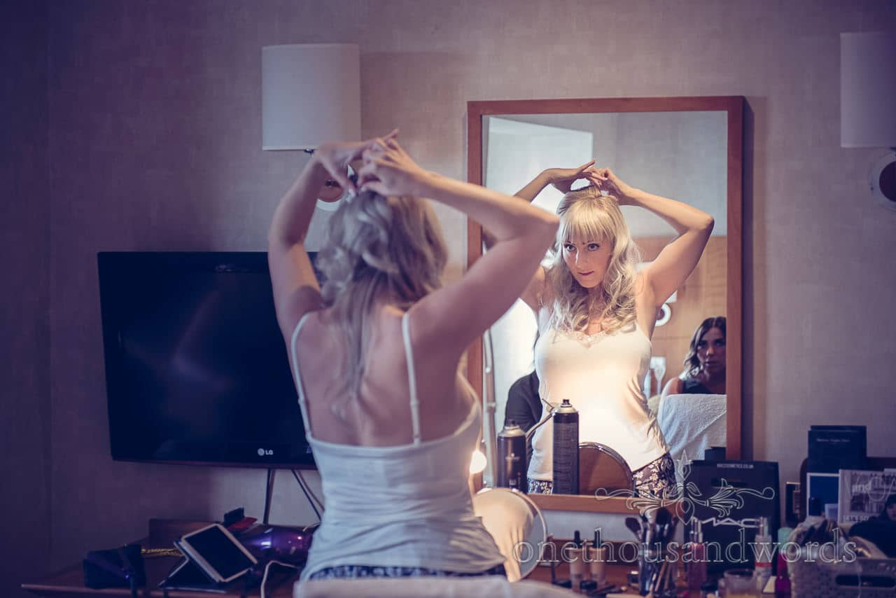 Bride styles her wedding hair in mirror on wedding morning at Harbour Heights
