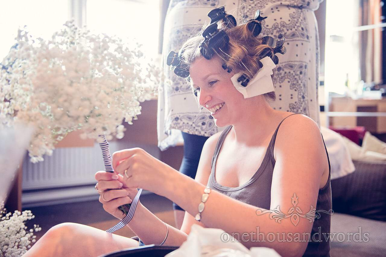Bride ties bue striped ribbon around gypsophila wedding bouquets