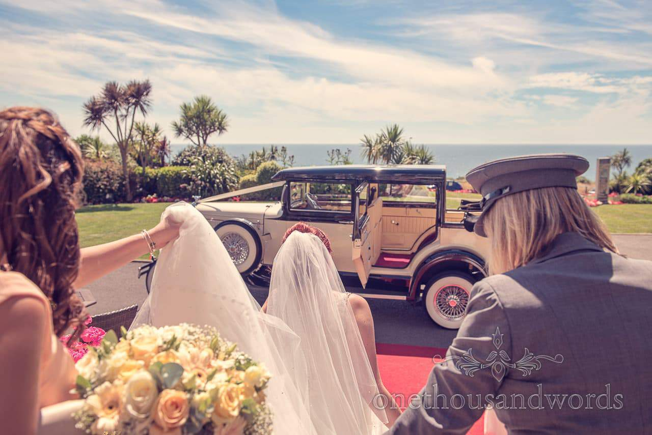 Bride walks to classic wedding car at Bournmouth Hotel wedding by the sea