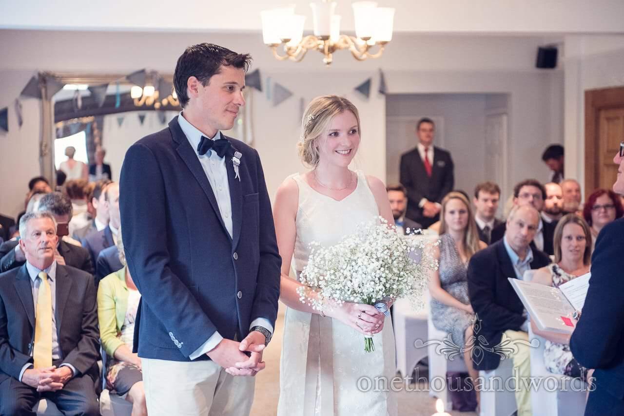 Bride with gypsophila bouquet and groom in blue wedding suit jacket