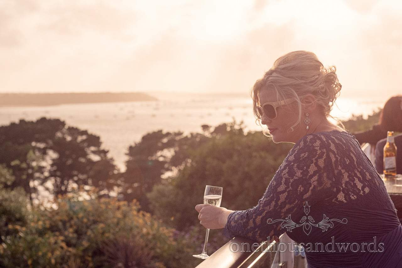 Bridesmaid in sunglasses enjoys sunset view at Harbour Heights Hotel wedding