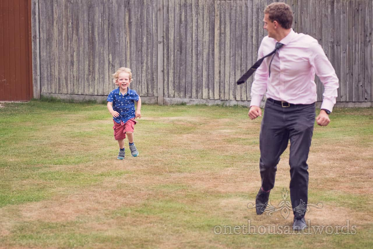 Child wedding guest plays a game of chase with his father at New Forest Wedding
