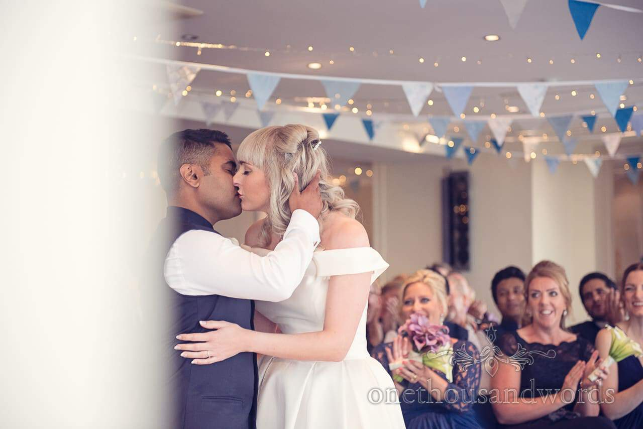 First kiss photograph under blue bunting at Harbour Heights Hotel Wedding