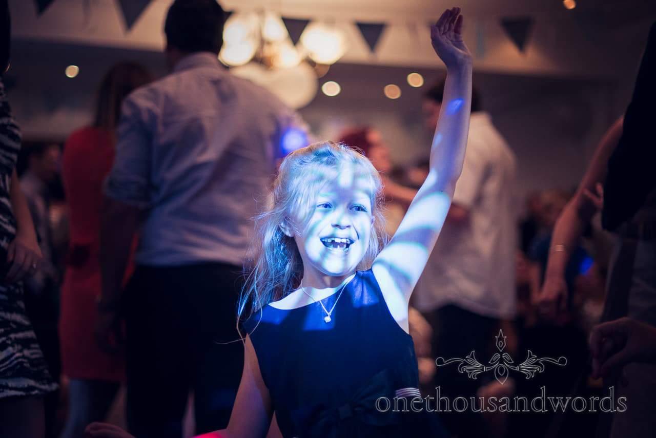 Flower girl dances in blue disco lighting at Balmer Lawn Hotel Wedding