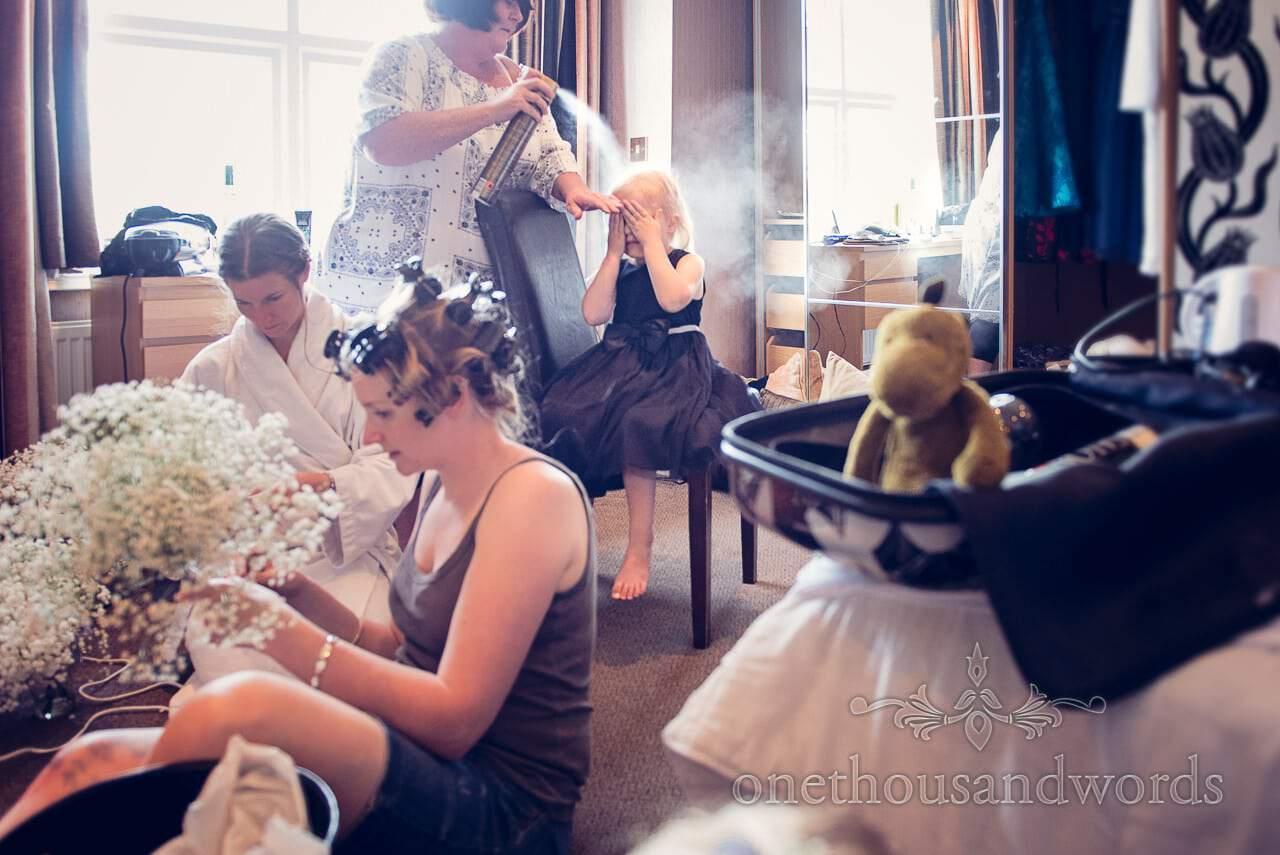 Flower girl has hair sprayed as bride makes gypsophila wedding bouquets