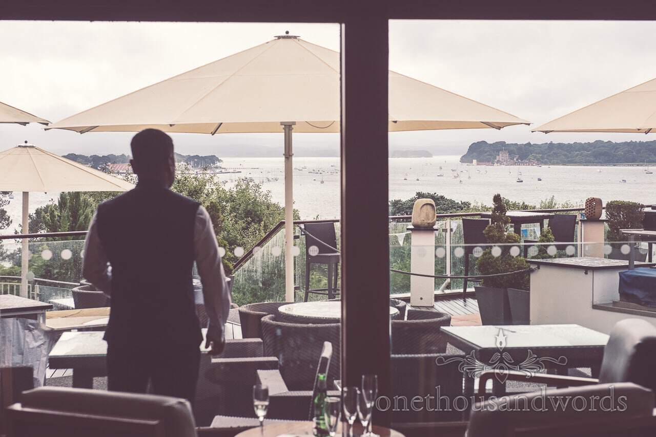 Groom admires the panoramic view at Harbour Heights Hotel Wedding