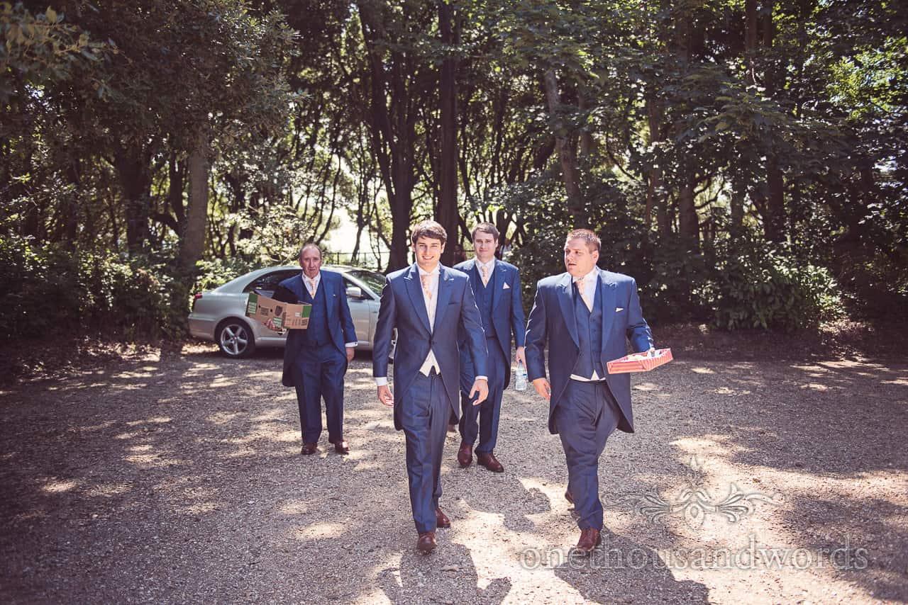 Groom and groomsmen in blue wedding suits walk to Highcliffe Castle wedding