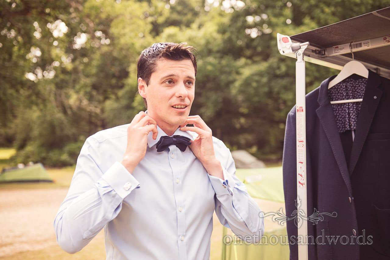 Groom puts on wedding shirt and bow tie in New Forest Campsite
