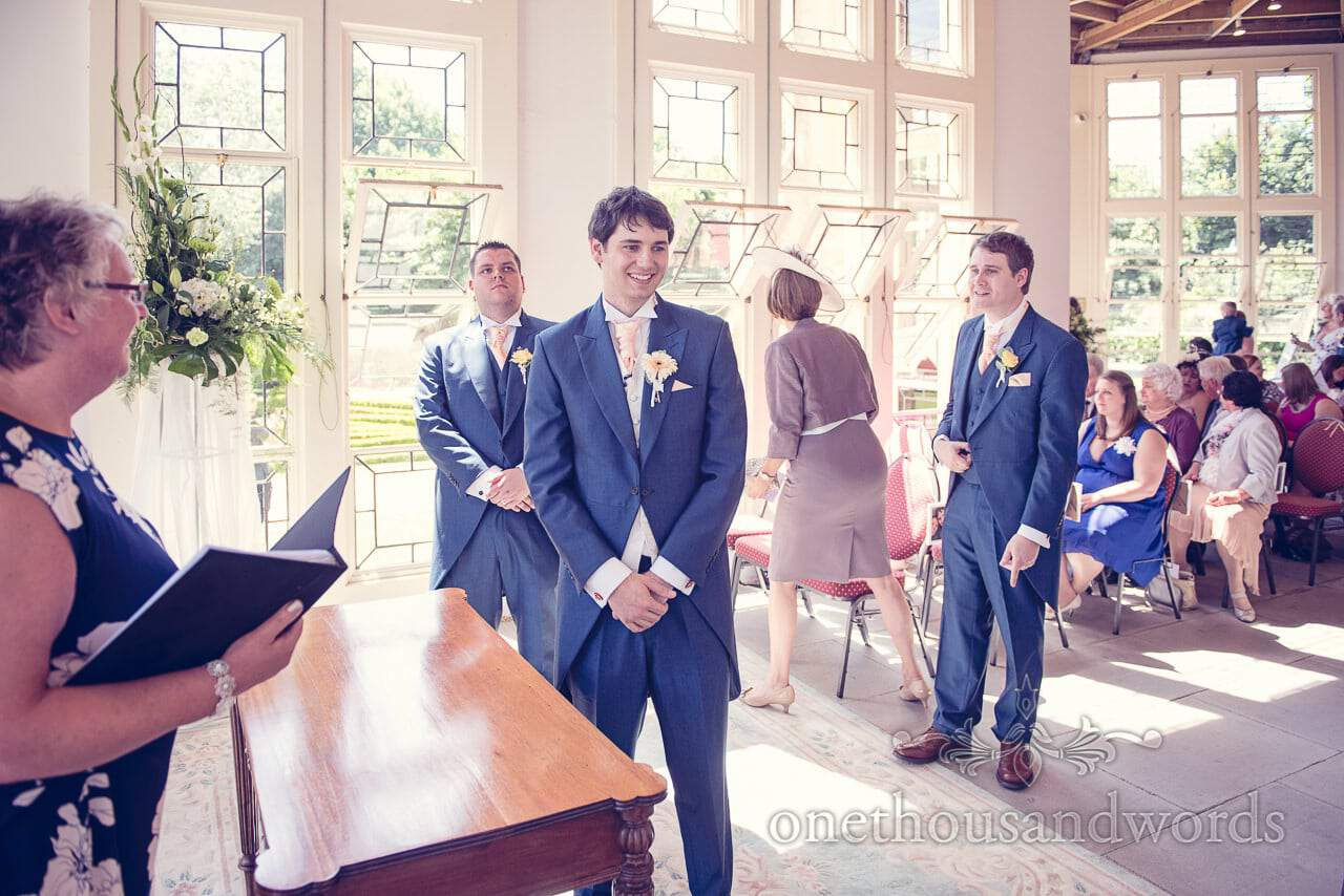 Groomsmen in blue wedding suits wait for bride at Highcliffe Castle wedding venue