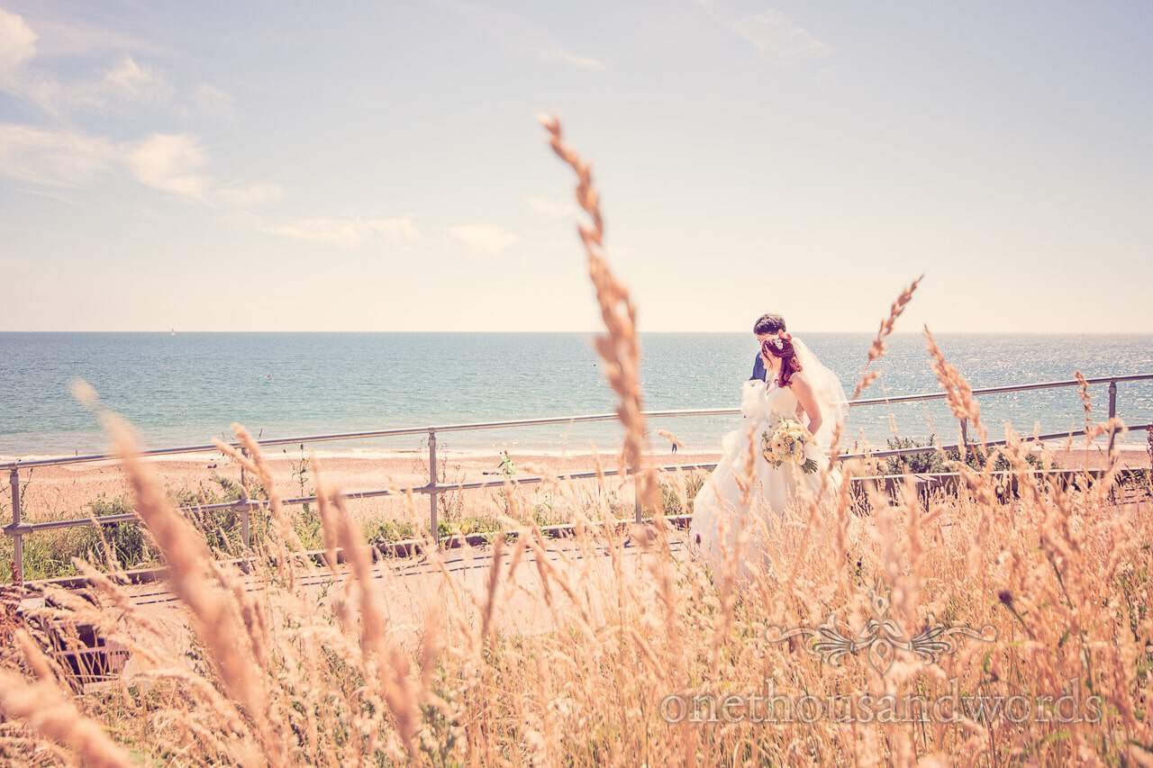 Newlyweds walk down to the beach from Bournemouth Hotel Wedding