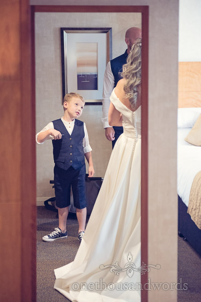 Page boy in blue sleveless wedding suit looks at bride in wedding dress