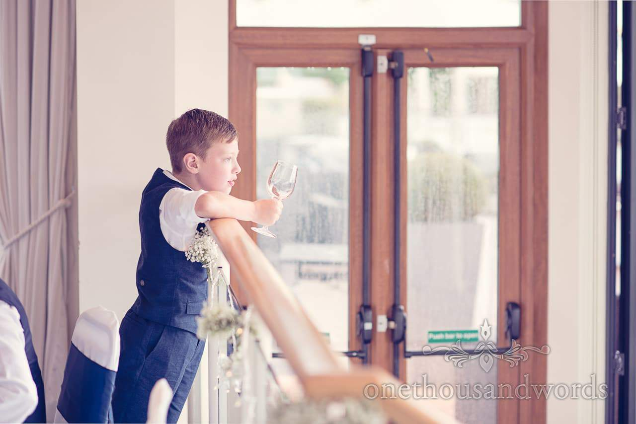 Page boy looks out to Brownsea Island during wedding speeches at Harbour Heights Hotel