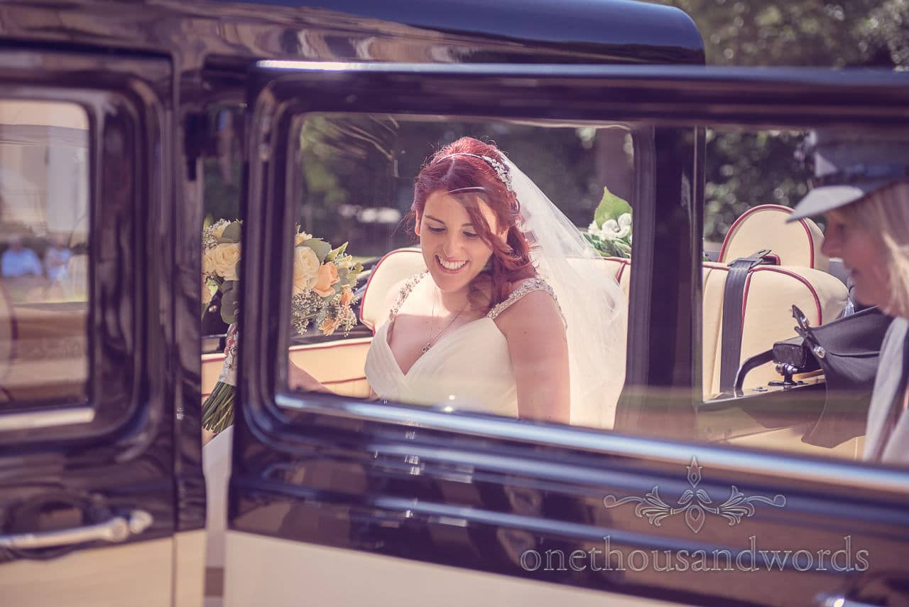 Red head bride arrives in classic wedding car at Highcliffe Castle wedding venue