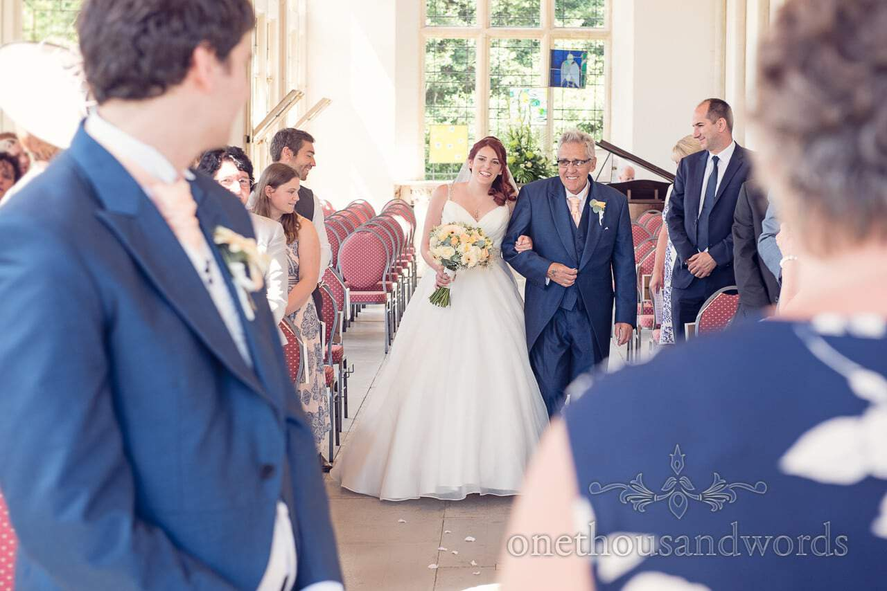 Red head bride walks down the aisle at Highcliffe Castle wedding ceremony