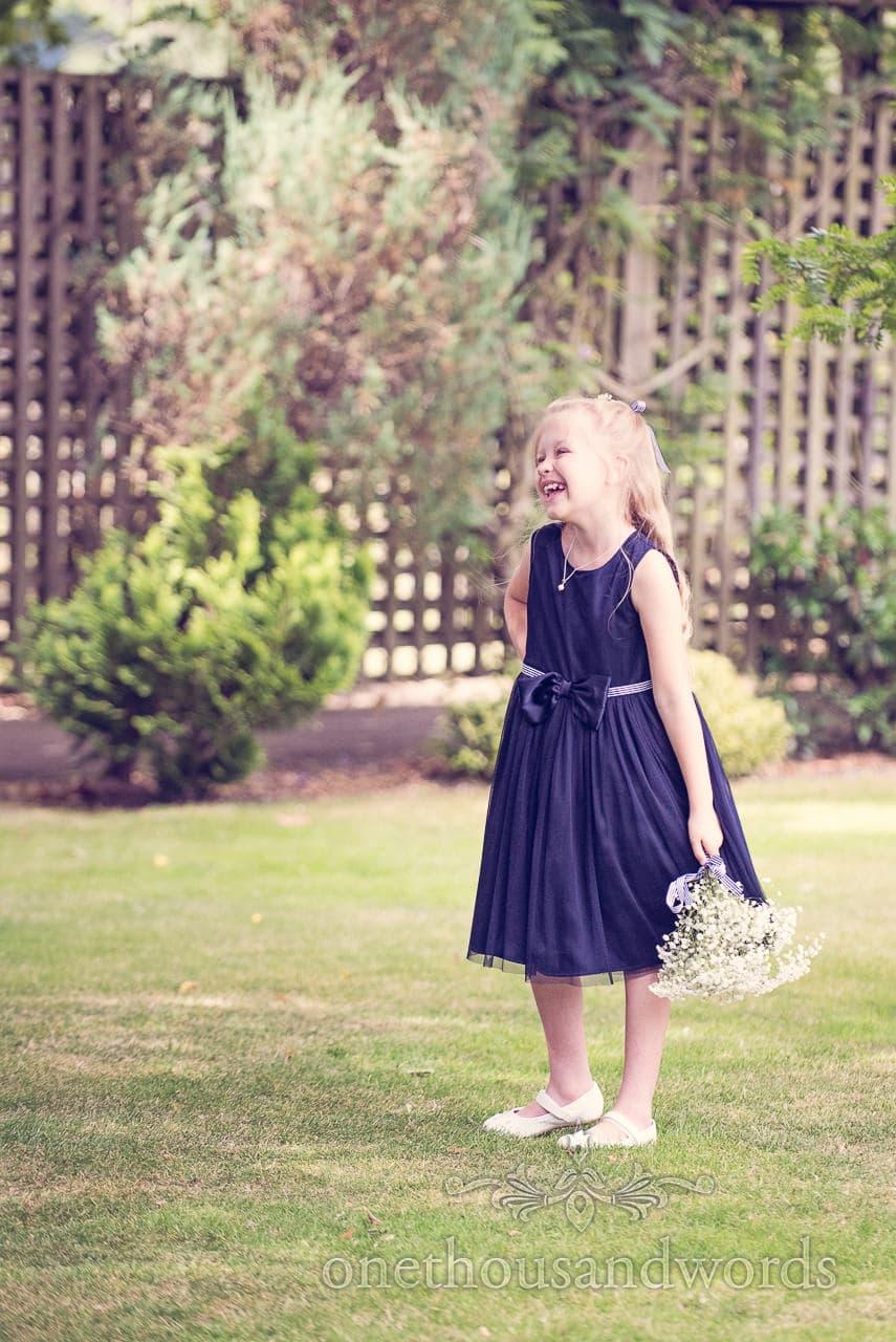 Wedding flower girl in blue dress at Balmer Lawn Hotel gardens