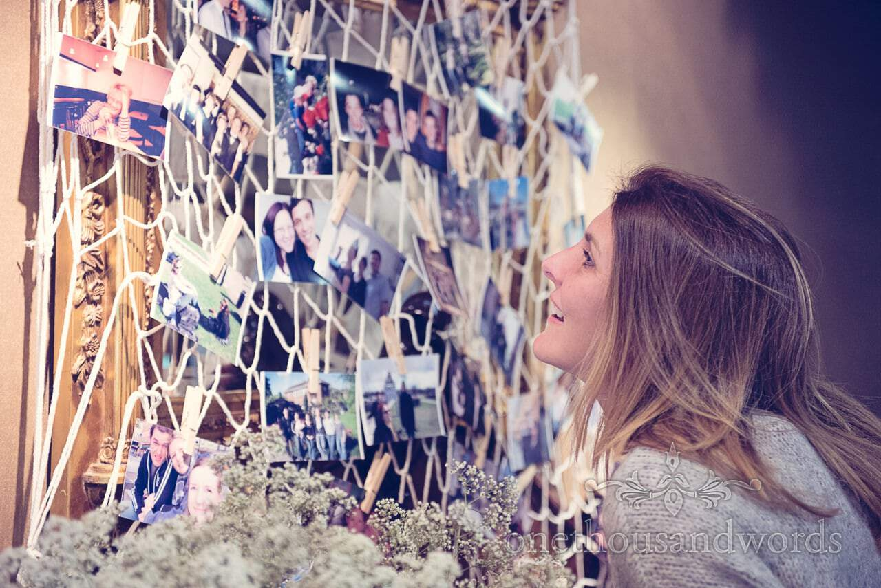 Wedding guest looks at family photographs fof bride and groom hung in fishing net