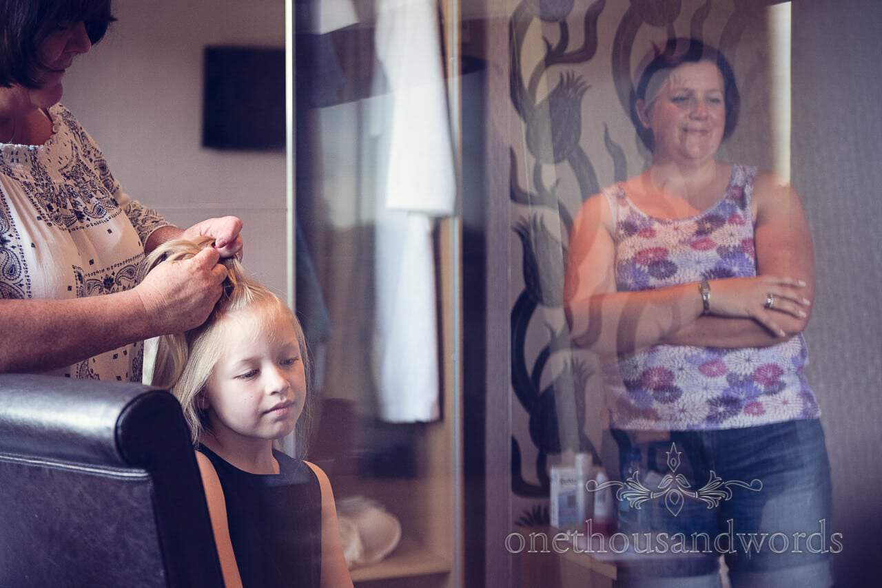 Wedding guest watches flower girl's hair being styled on wedding morning
