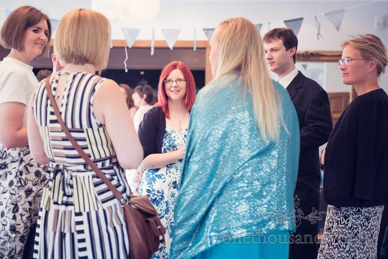 Wedding guests chat beneith blue bunting at Balmer Lawn Hotel Wedding