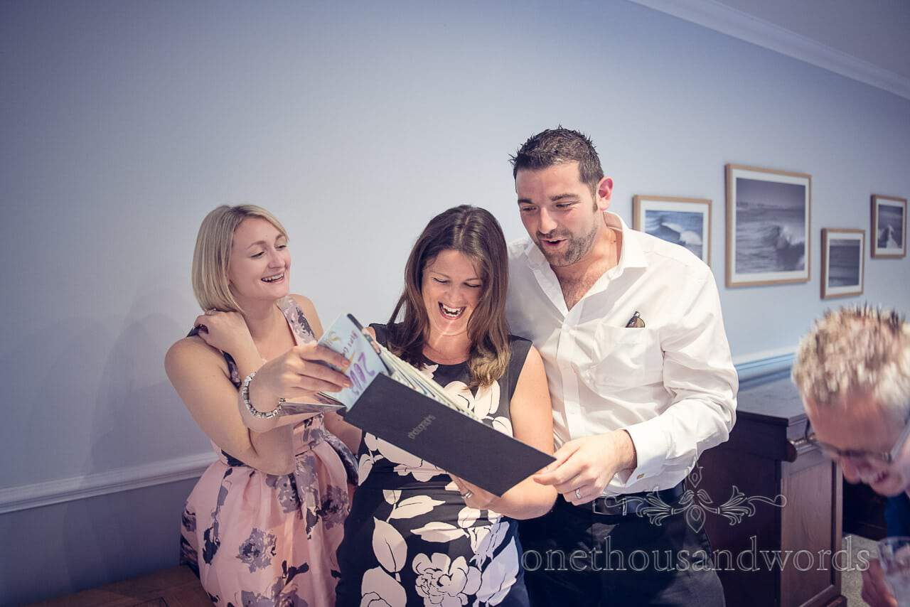 Wedding guests laugh at bride and grooms family photographs