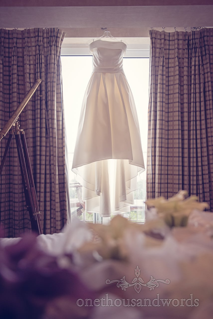 White 1950's retro wedding dress hangs in window at Harbour Heights Hotel Wedding
