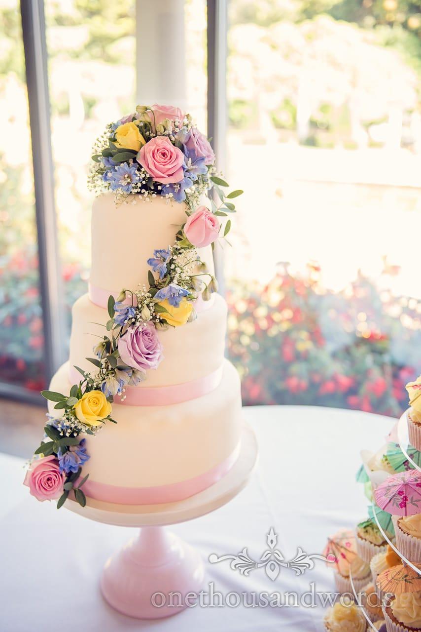 3 tier white wedding cake with pastel flowers spray at italian villa wedding