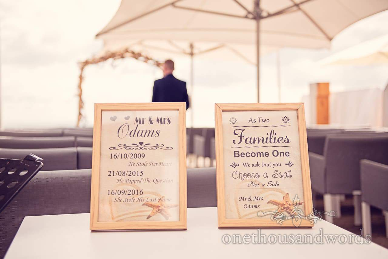 As two families become one signs at seaside theme wedding in Dorset