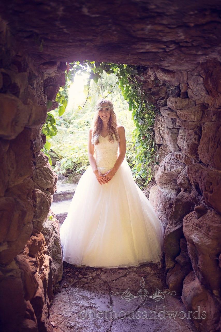 Beautiful Blonde bride in wedding dress in garden cave at italian villa wedding photographs