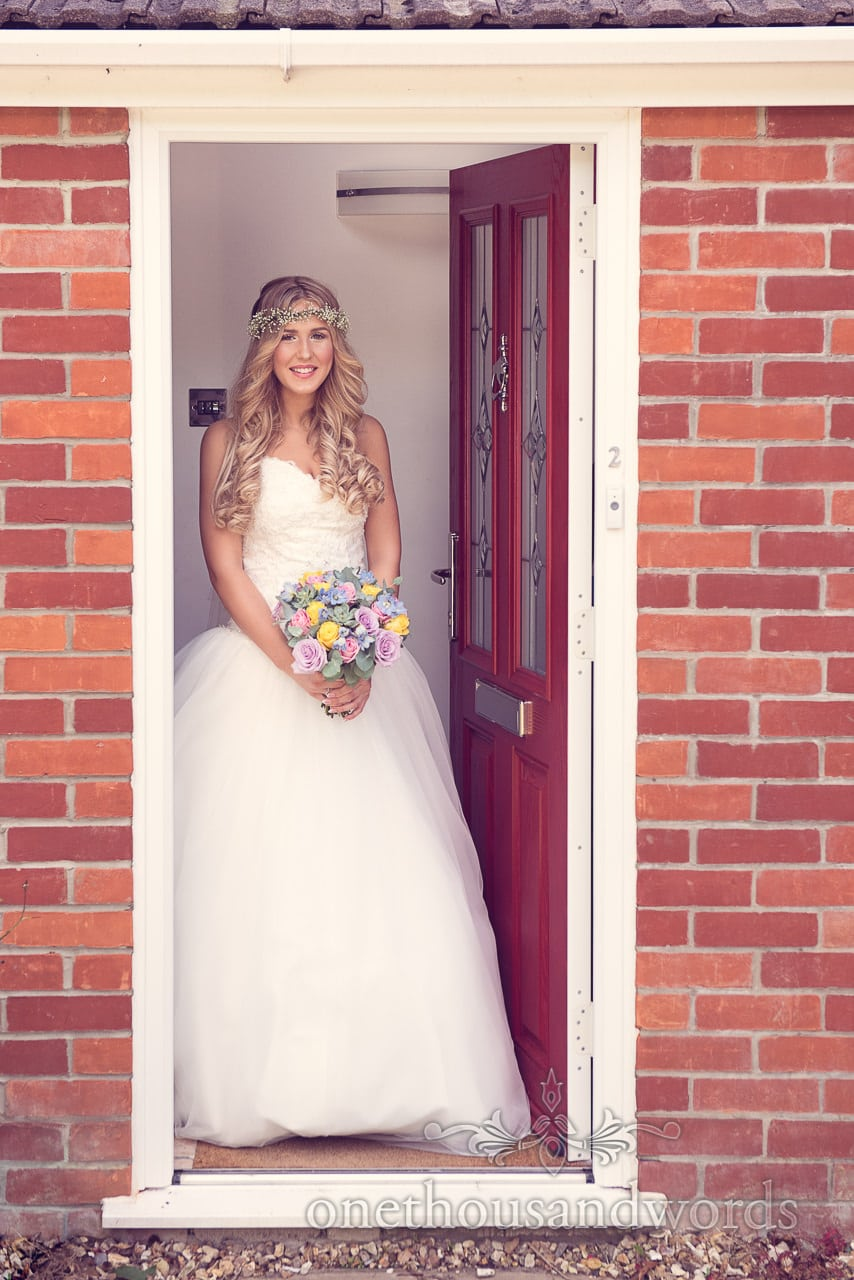 Beautiful blonde bride with gypsophila hair band and pastel wedding bouquet in white wedding dress in Doorway