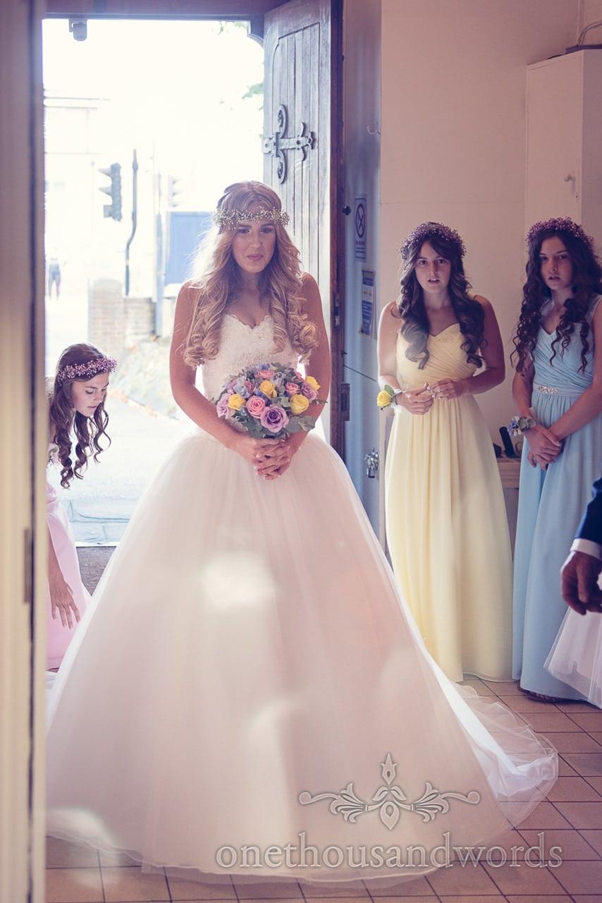 Beautiful bride waits with bridesmaids in church doorway before wedding ceremony