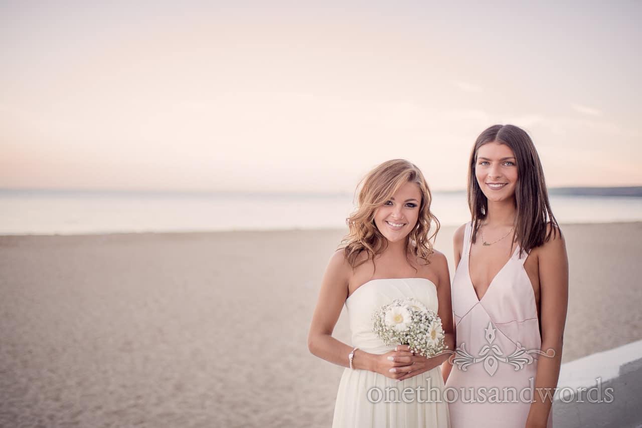 Beautiful bridesmaid and friend by the beach at Sandbanks Hotel Wedding sunset