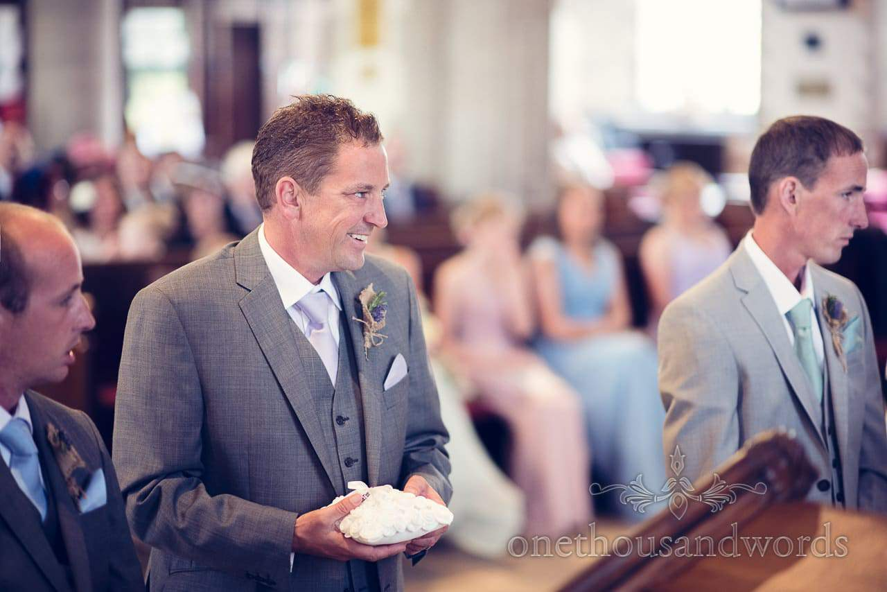 Best man smiles with wedding rings on pillow at Swanage church wedding ceremony