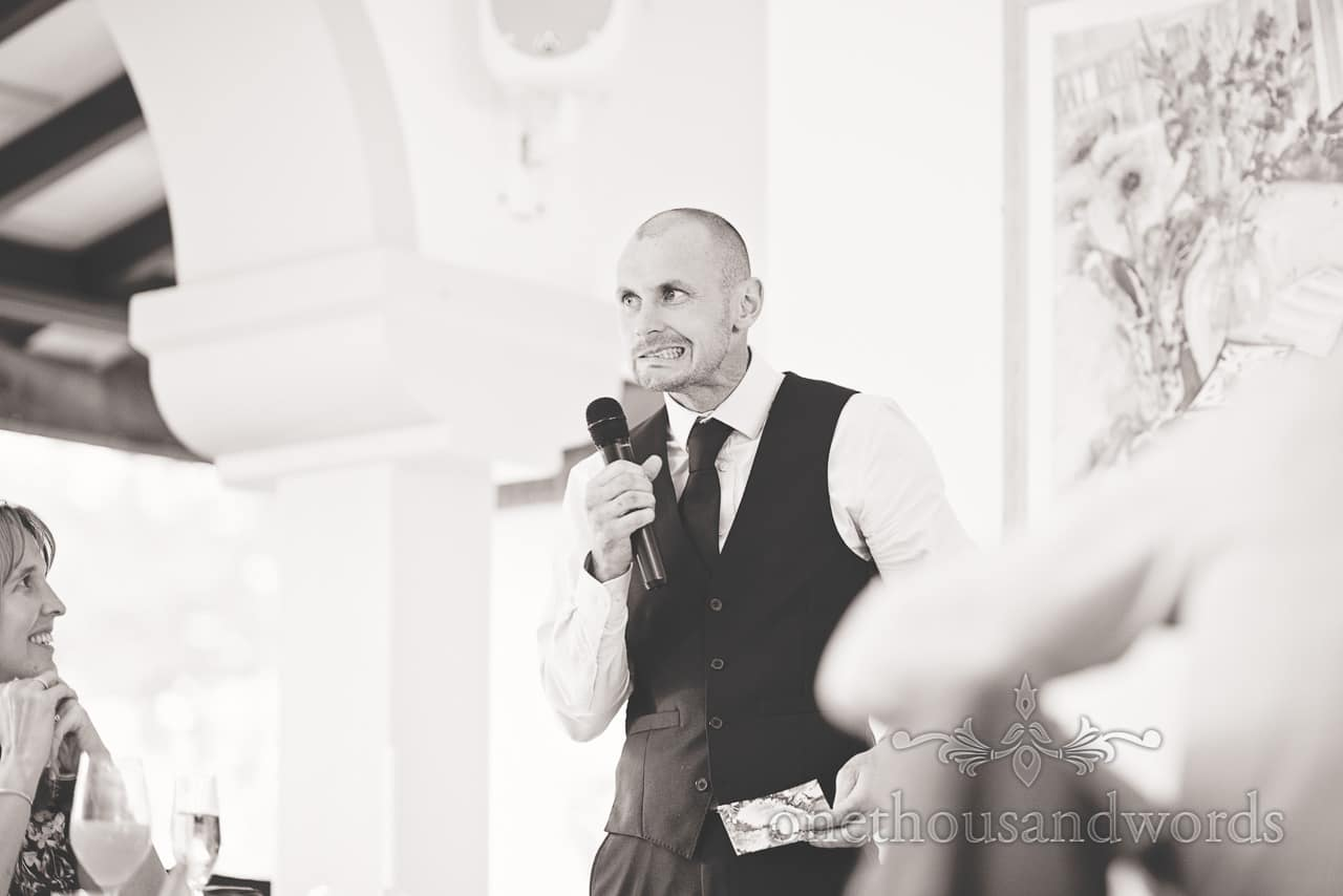 Black and white wedding photograph of best man pulling a face during best mans speech