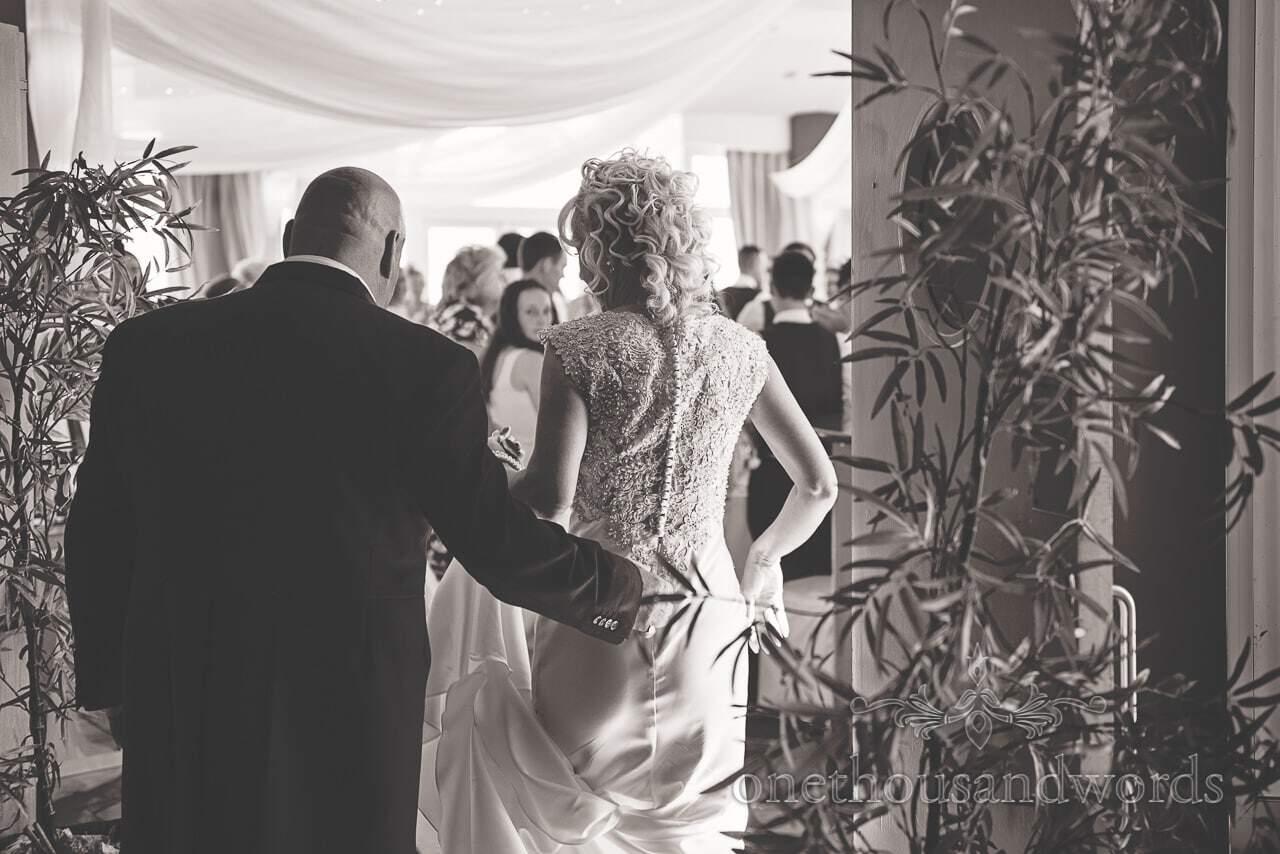 Black and white wedding photograph of bride and groom entering Sandbanks Hotel Wedding breakfast