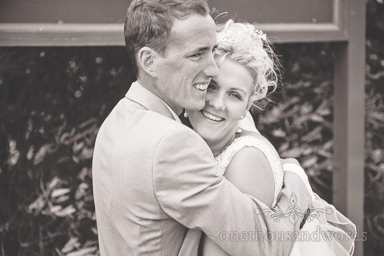 Black and white wedding photograph of bride and groom hugging
