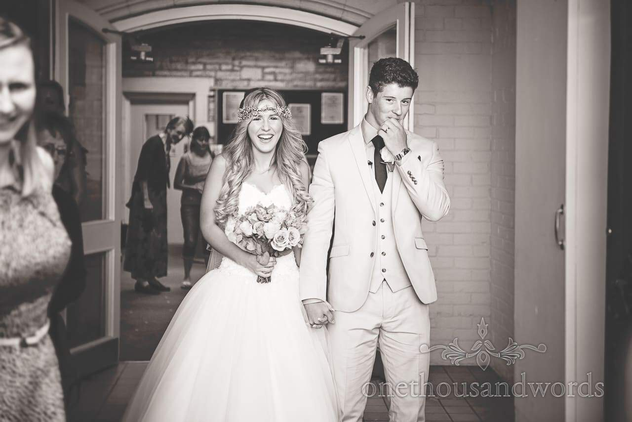 Black and white wedding photograph of bride and groom leaving church