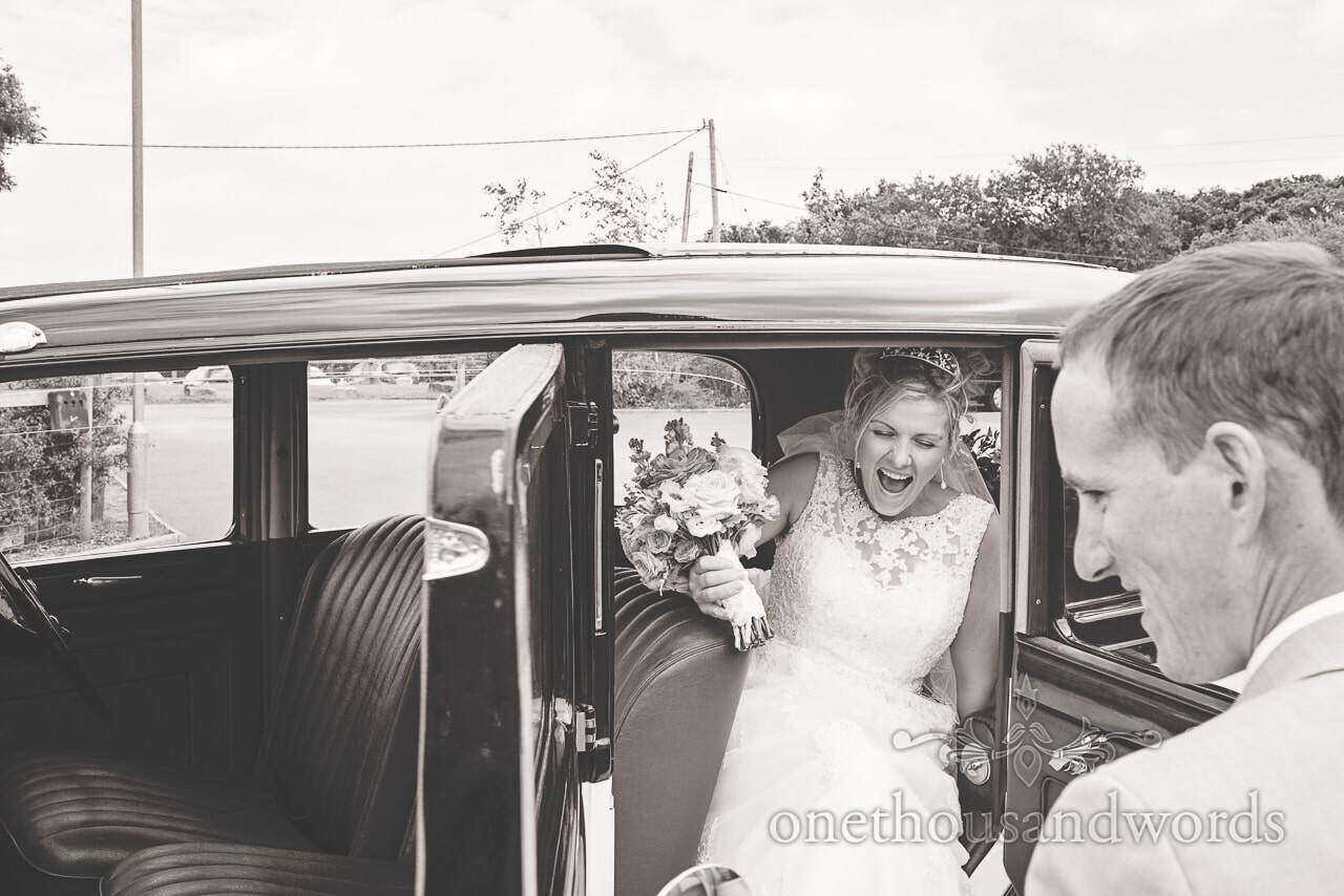 Black and white wedding photograph of bride laughing as she leaves classic wedding car