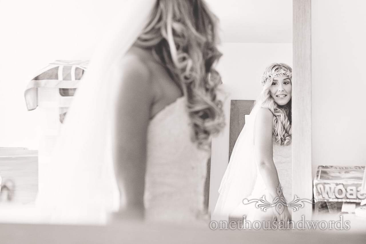 Black and white wedding photograph of bride looking in mirror on wedding morning