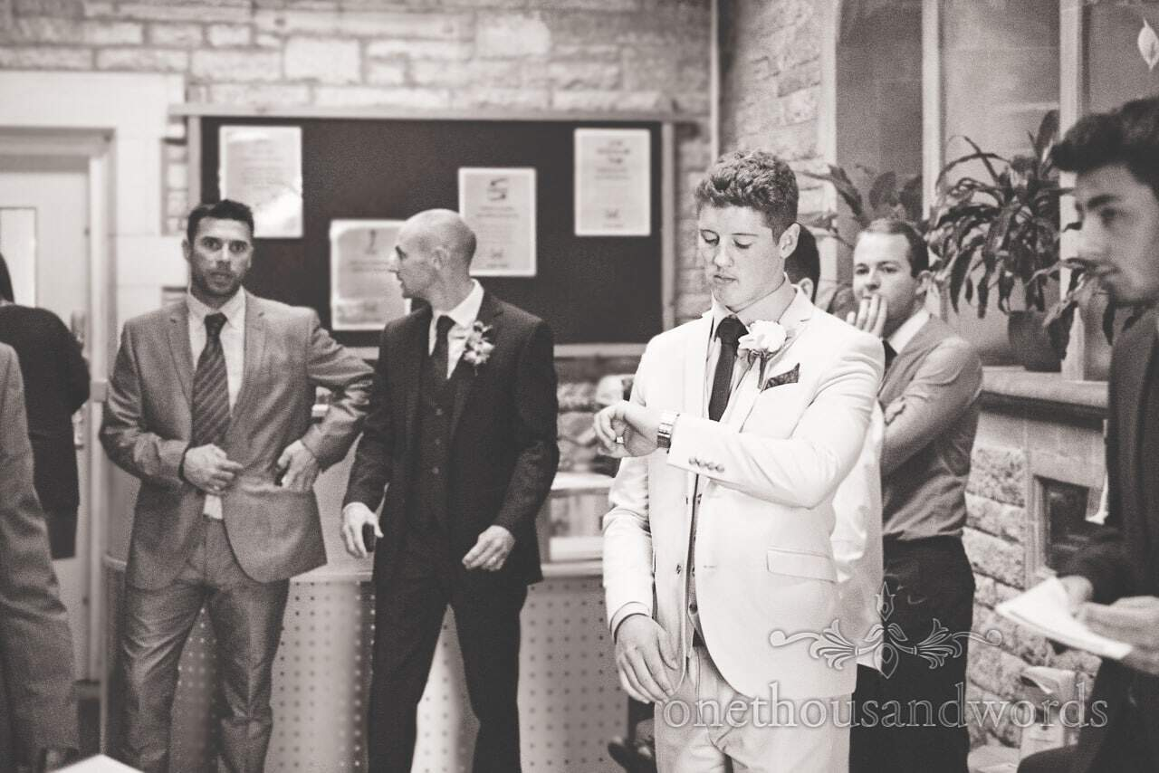 Black and white wedding photograph of nervous groom checking his watch before wedding