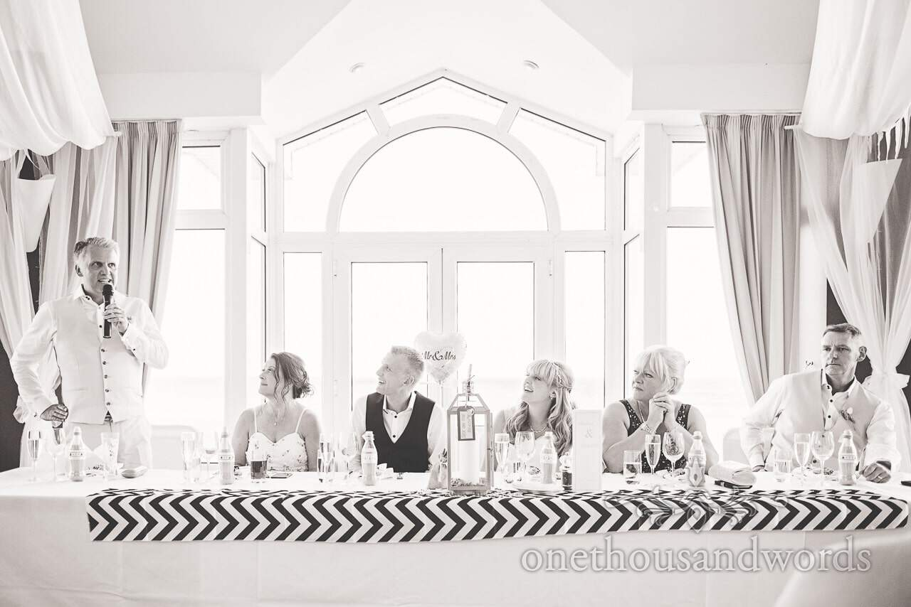 Black and white wedding photograph of speeches at Sandbanks Hotel wedding