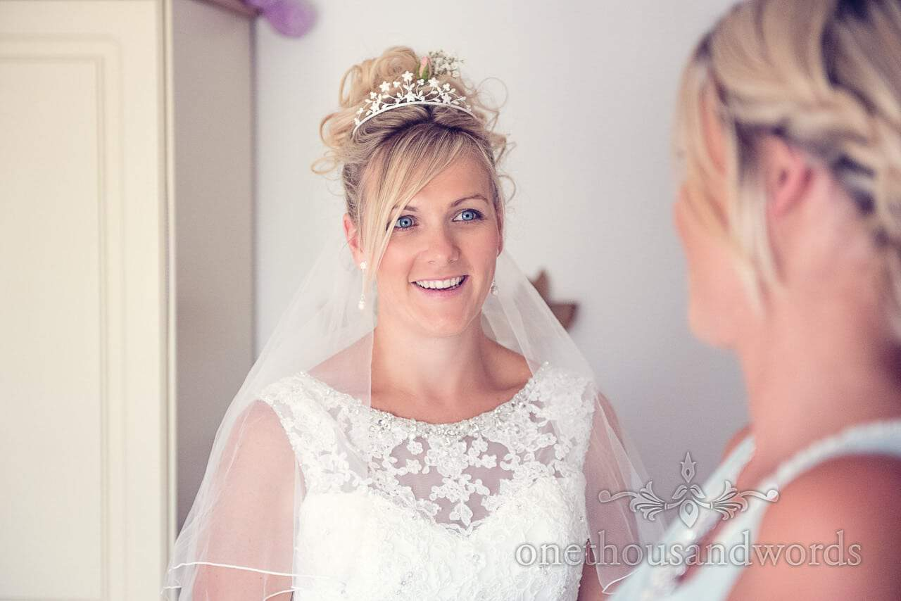 Blonde blue eyed bride in detailed ivory wedding dress with tiara and flowers in hair