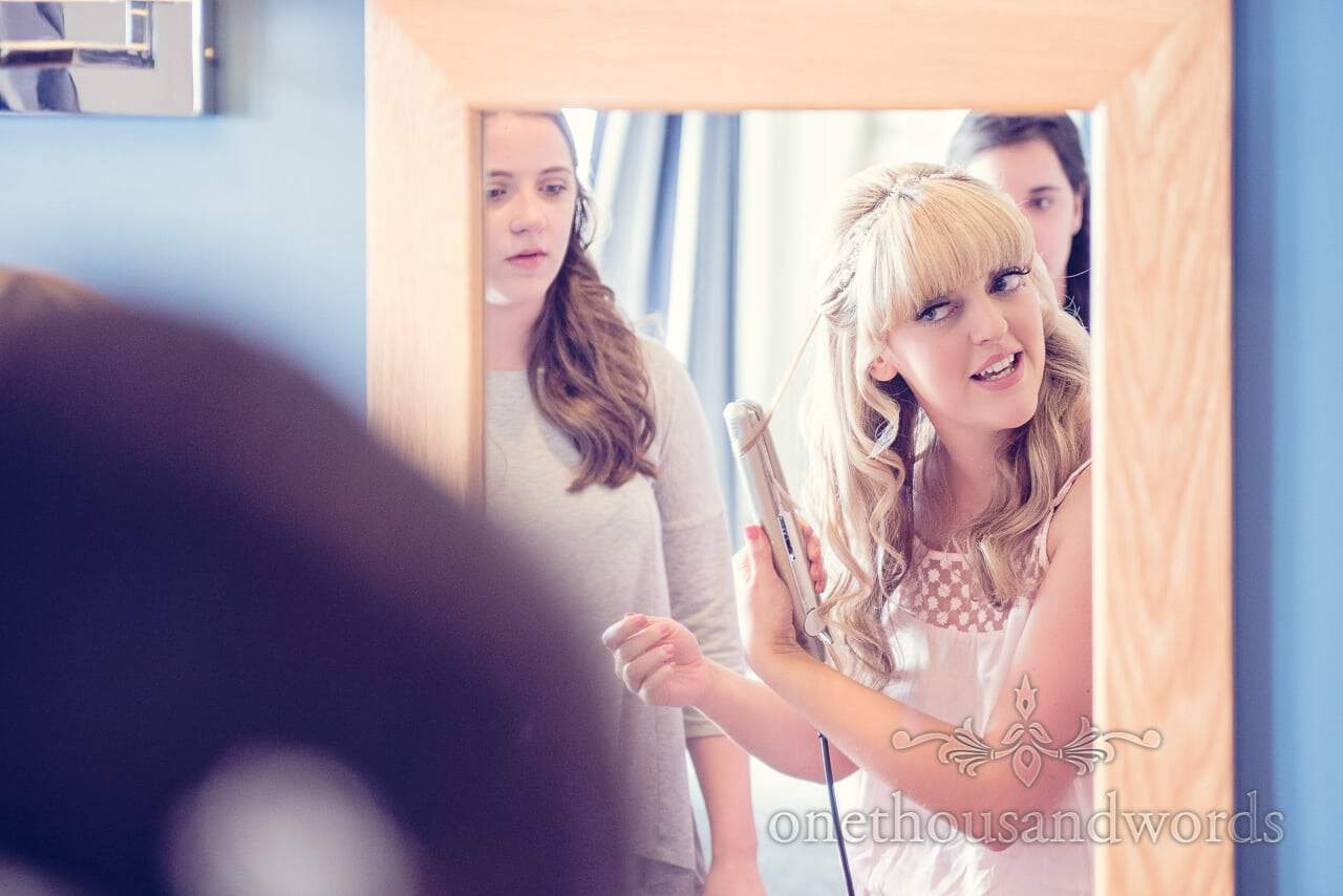 Blonde bride curls wedding hair in mirror at Sandbanks Hotel wedding