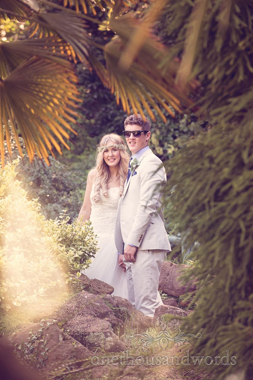 Blonde bride in floral head piece and groom in sunglasses in tropical gardens